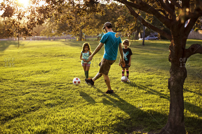 Father playing soccer with his children in a grassy park