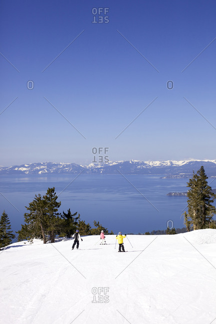 Three children ski down a hill