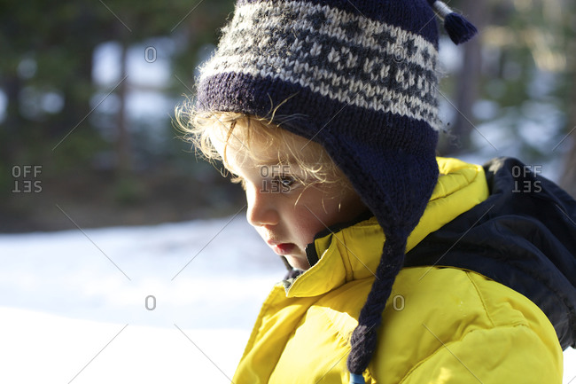 A young boy stands in snow