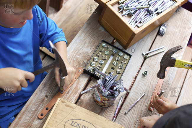 A young boy stamps leather