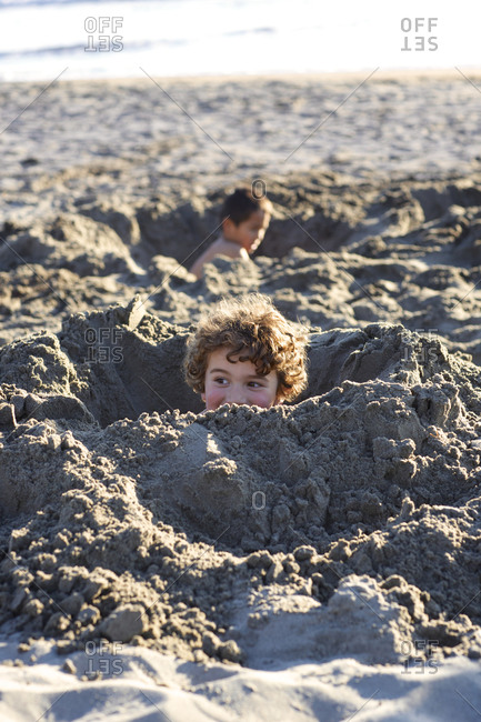 Boys play in giant holes on sandy beach