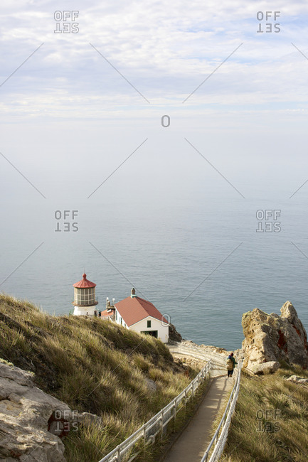 People walk down a pathway down to a lighthouse