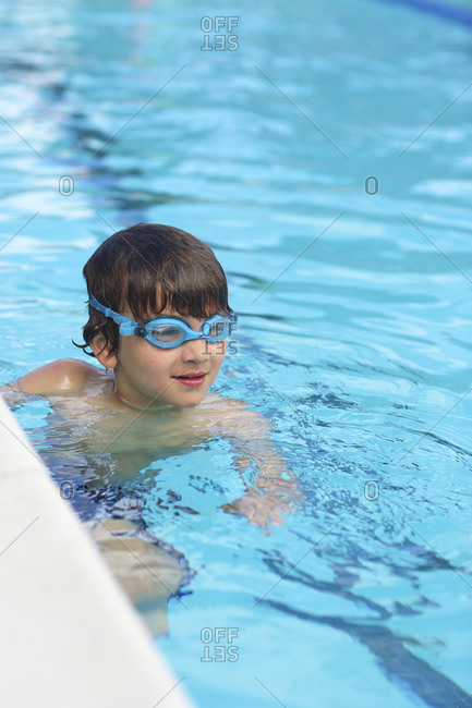 A boy hangs on to the wall of a swimming pool