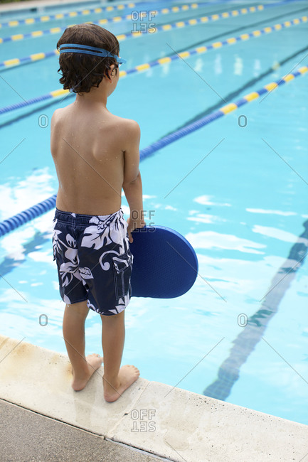 A young boy stands by swimming pool