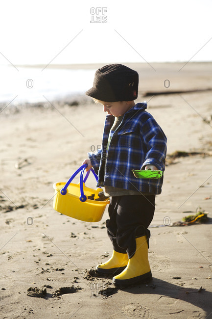 A toddler at beach with bucket