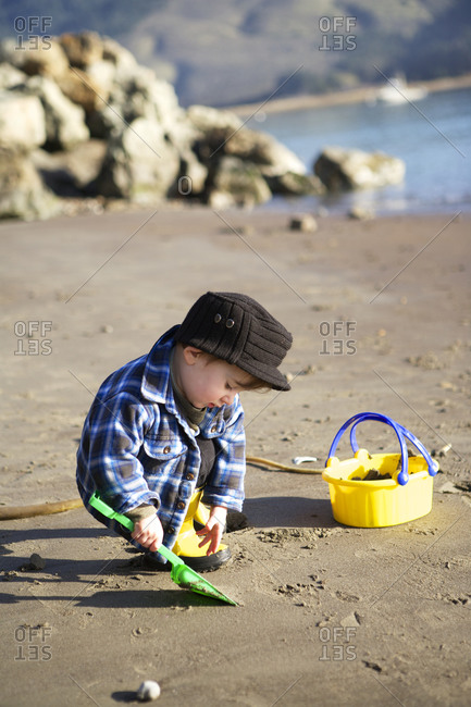 A toddler digging at the beach