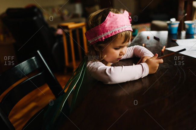 Young girl in dress up wings drawing at table