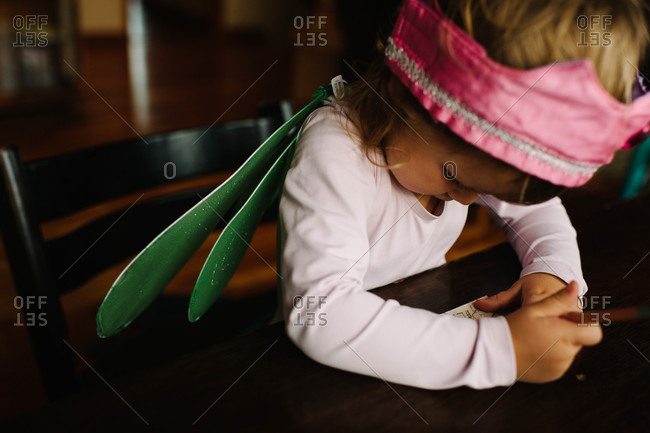 Young girl drawing at a table in costume