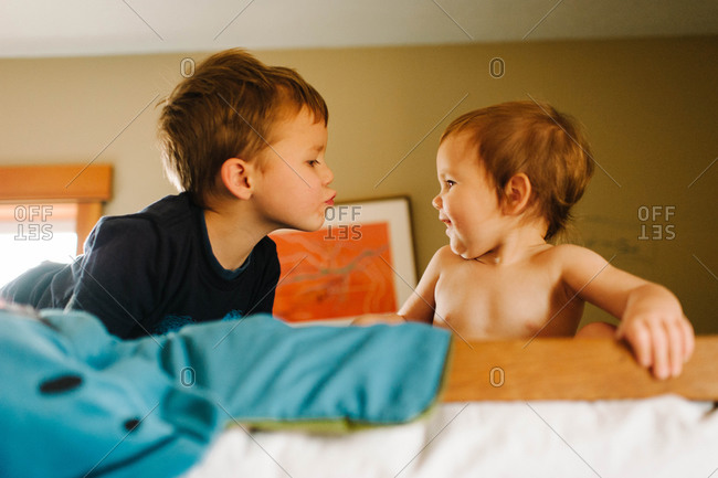A boy gives a kiss to a toddler