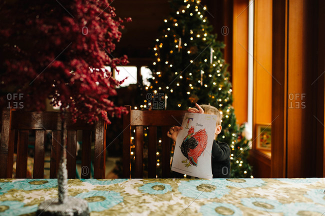 Boy holding up drawing with Christmas decorations