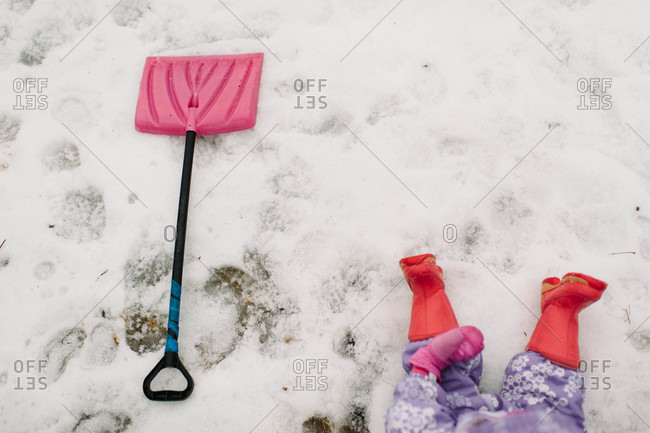 Child and snow shovel lying on snowy ground