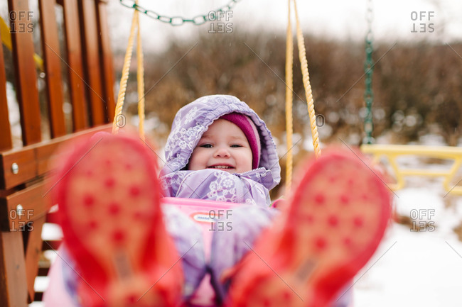 A young child in snowsuit on swing in winter