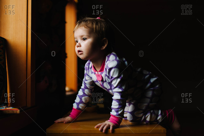 A child in pajamas looking out window