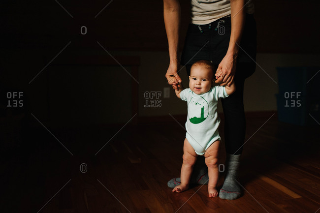 A man supporting a standing baby