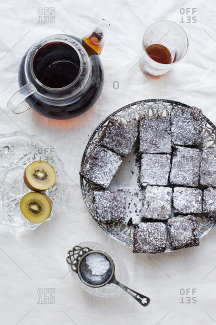 Brownies on a silver plate with tea and kiwi