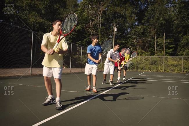 Boys on tennis court about to serve