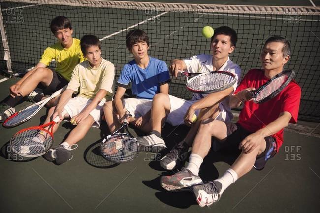 Boys and man resting at tennis net