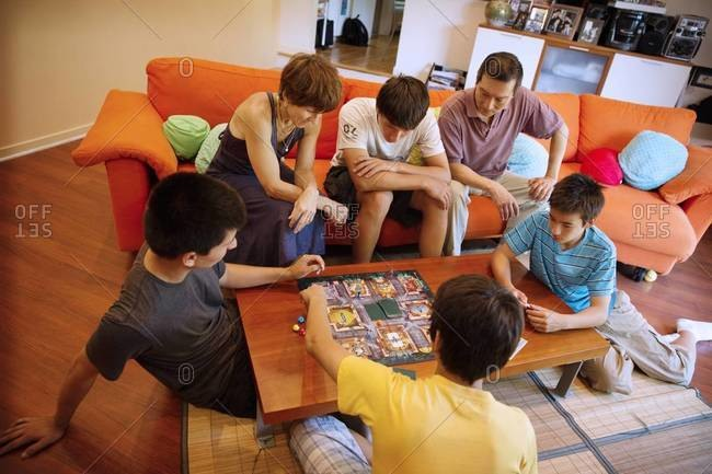 Family playing board game at coffee table