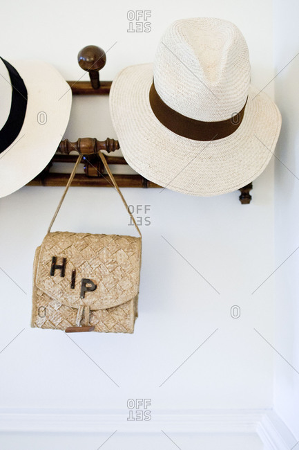 Hats and a purse hanging on wall hooks