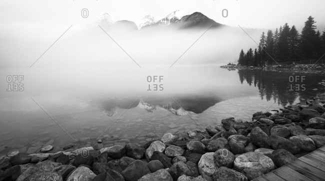 Heavy fog over lake with rocky shore