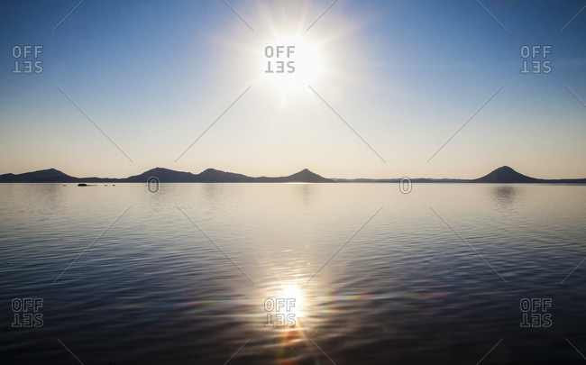 Bright setting sun reflected in lake