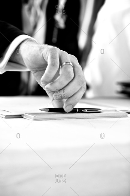 Groom reaching for pen to sign wedding certificate