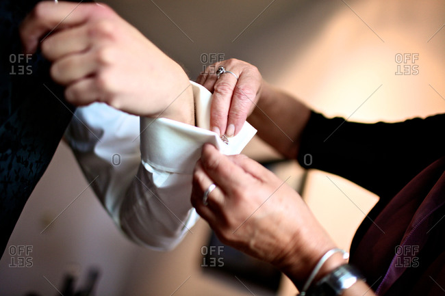 Woman helping man secure cufflinks before a wedding