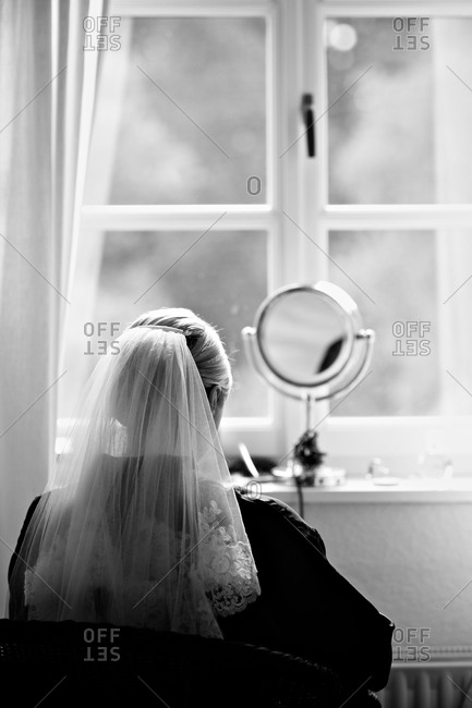 Bride using make-up mirror to prepare for wedding