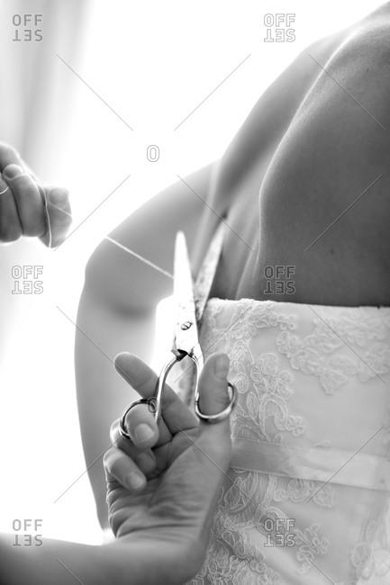 Woman cutting of thread of bride's wedding dress