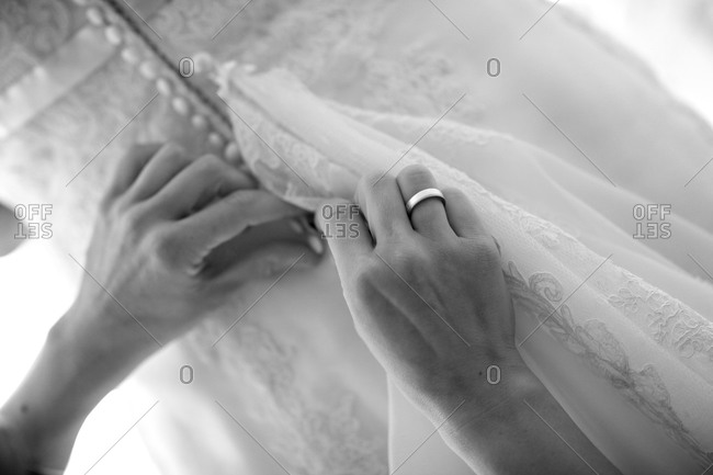 Woman helping bride do up her dress before the wedding