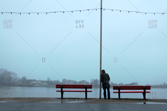 Man leaning against lamppost looking over the water