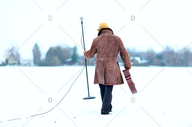 Man with guitar setting up mic stand out in the snow
