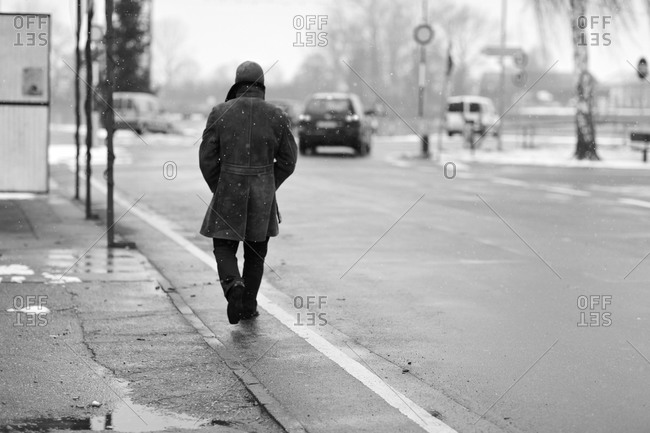Man walking by the street in the snow