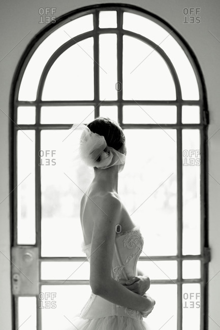 Bride looking out arched window