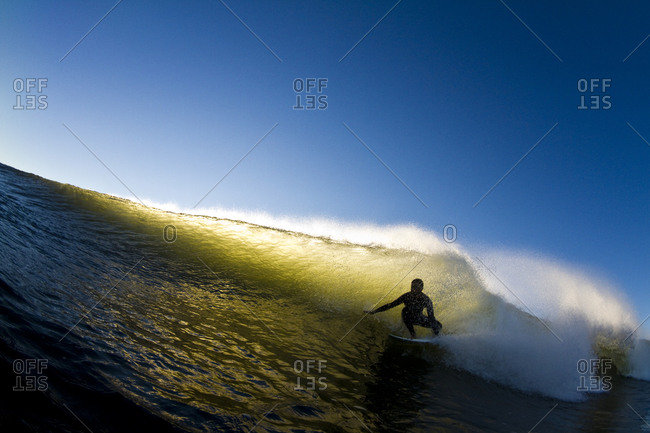 Silhouette of surfer riding wave