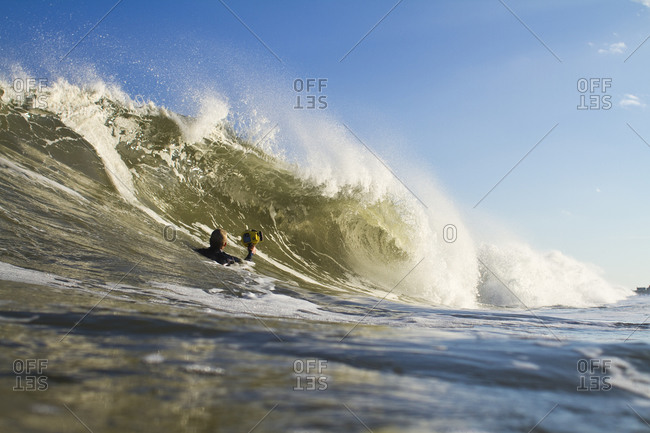 Man in ocean taking picture of wave