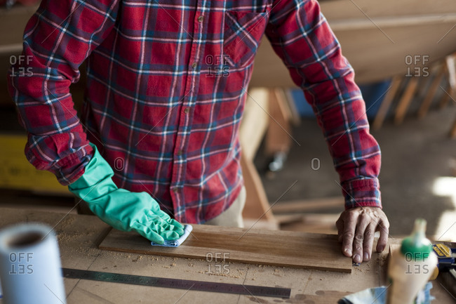 Man staining a piece of wood in workshop