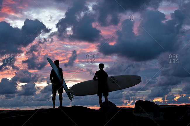 Two men with surfboards backlit by sunset