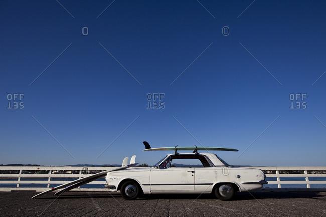 Classic car and surfboards near ocean