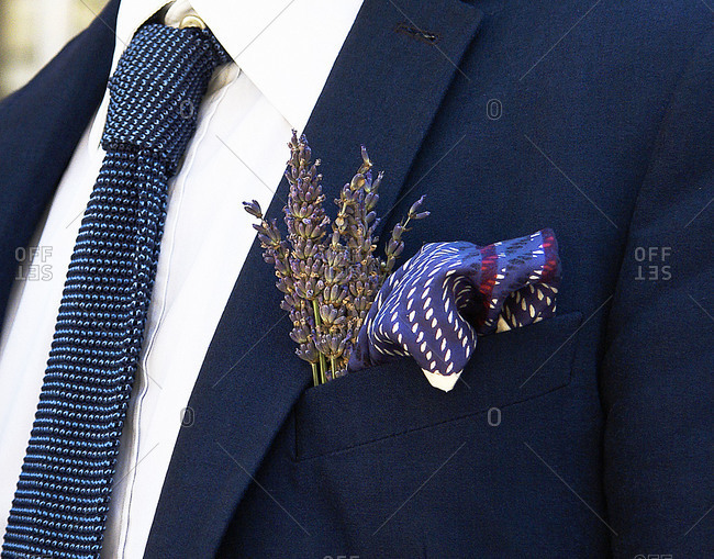 A man wears a pocket square and flowers in his suit