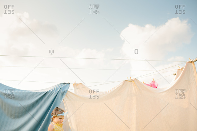 A girl playing in laundry on line