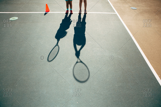 Long shadows of kids with tennis racquets