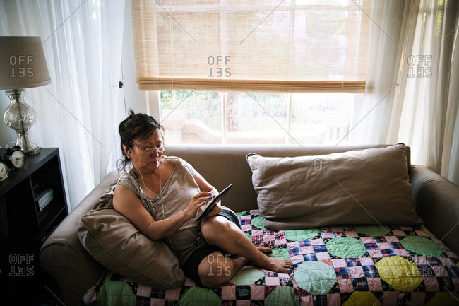 Woman on loveseat listening to tablet