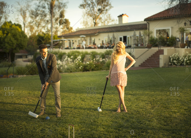 A smart young man hits a croquet ball with a mallet, a beautiful lady watches him from a distance with a mallet in her one hand and legs cross