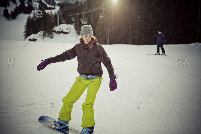 A young woman snowboarding on Whistler Mountain