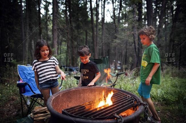 Children standing around a fire pit in the forest