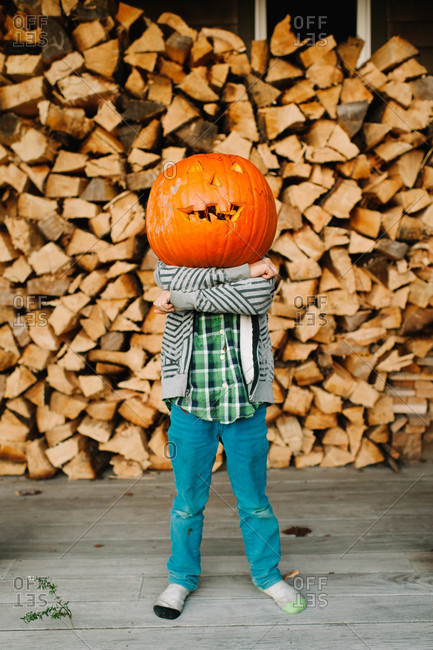 Portrait of a young boy with a pumpkin mask