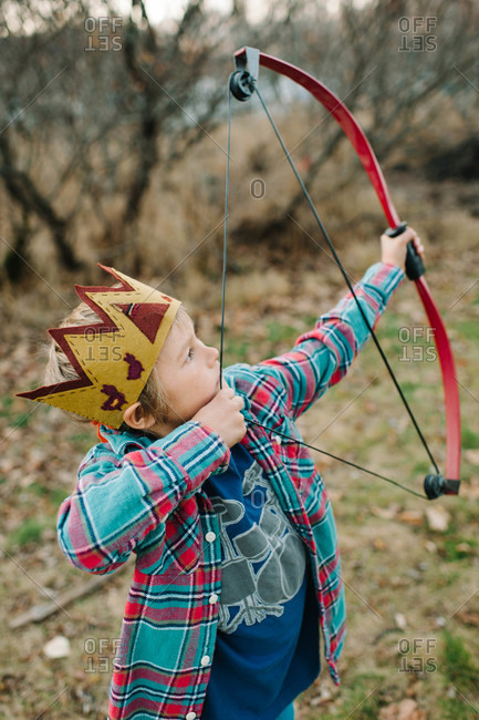 Young boy with a crown aiming with a bow