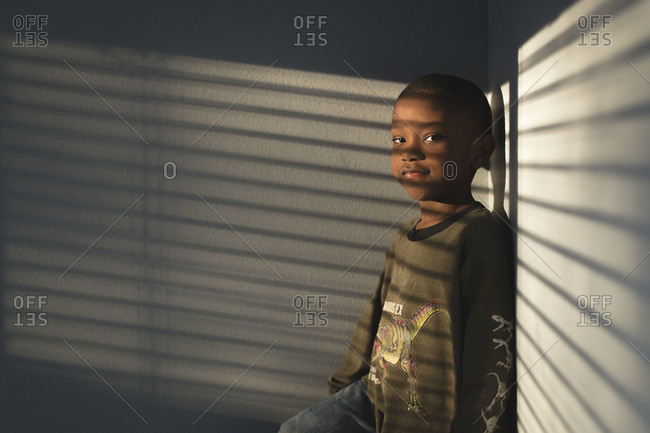 Boy in corner with light from window