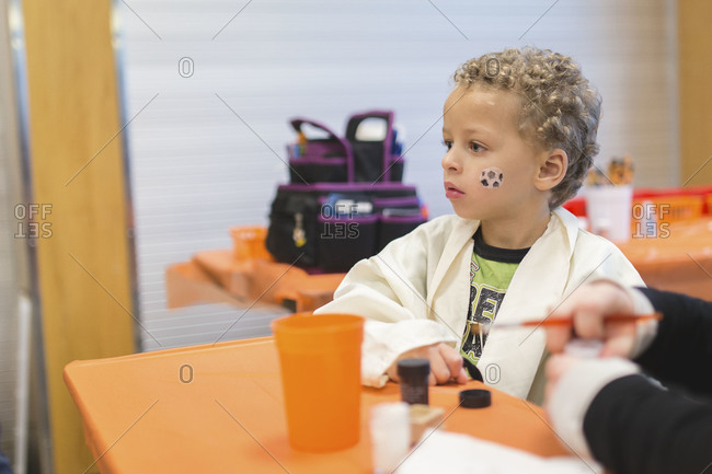 Woman painting face of little boy in costume